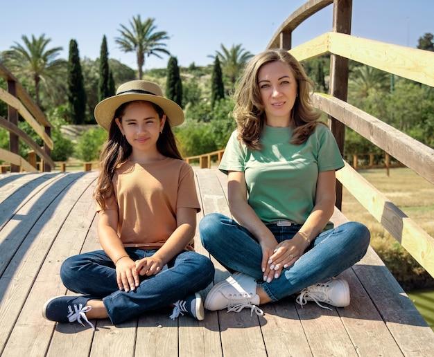 晴れた日に公園の木造橋に足を組んで座っている母と娘。シャツとジーンズの中年女性と子供の女の子。 tシャツのモックアップ。夏に一緒に時間を過ごす家族