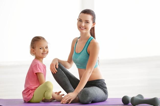엄마와 딸이 체육관에 앉아 있다