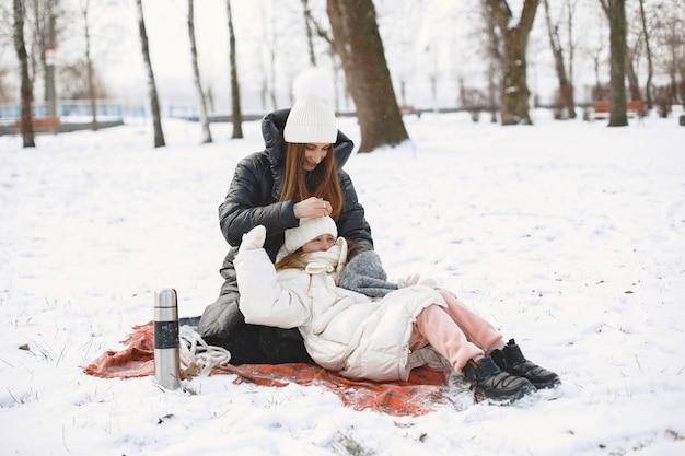 엄마와 딸 눈 덮인 공원에 담요에 앉아