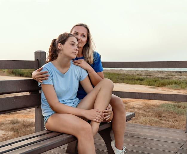 엄마와 딸은 일몰에 함께 나무 벤치에 앉아 있습니다. 10대 소녀를 껴안은 웃는 중년 여성. 티셔츠 모형