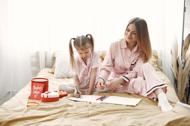 ベッドに座っている母と娘。子供の絵、母親が彼女を助けています。母の日おめでとう。