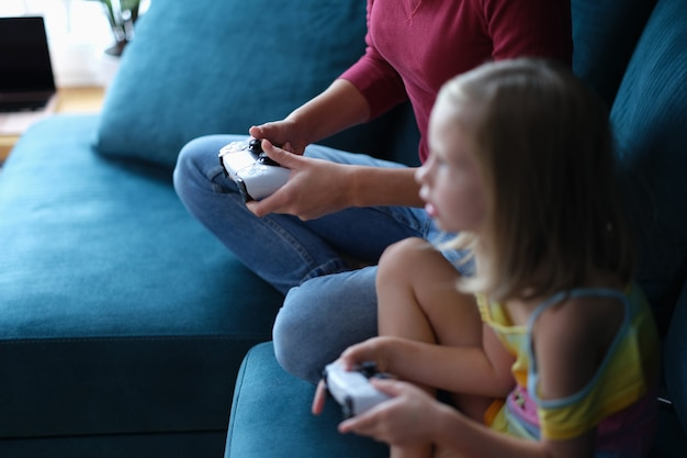 엄마와 딸이 소파에 앉아 조이스틱으로 컴퓨터 게임을 하고 있다
