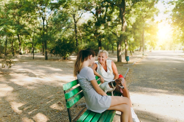 엄마와 딸이 작은 재미있는 강아지와 함께 벤치에 앉아 있습니다. 작은 잭 러셀 테리어 애완동물이 공원에서 야외에서 놀고 있습니다. 개와 여자. 야외에서 쉬고 있는 가족.
