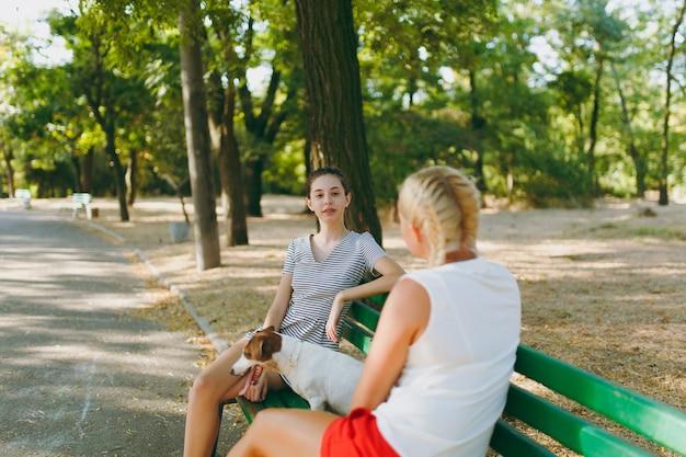 小さな面白い犬と一緒にベンチに座っている母と娘。公園で屋外で遊ぶリトルジャックラッセルテリアのペット。犬と女性。戸外で休んでいる家族。