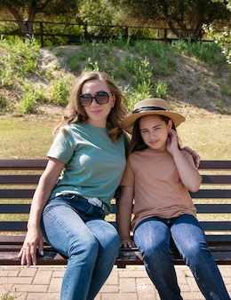 晴れた日に公園の木製のベンチに座っている母と娘。シャツとジーンズを着た中年の女性と子供の女の子。 tシャツのモックアップ。夏に一緒に時間を過ごす家族