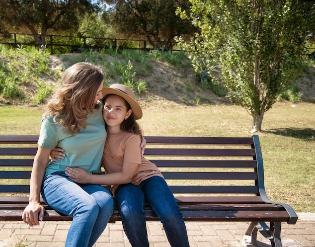公園の木製のベンチに座っている母と娘