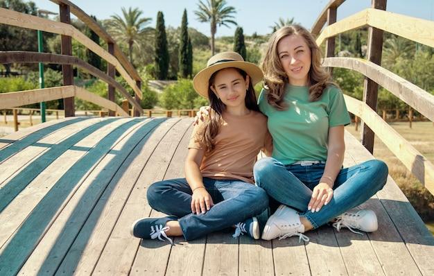 公園の木造橋に座っている母と娘