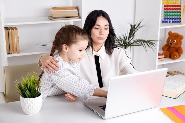 Мать и дочь, сидя с компьютером вместе за столом.
