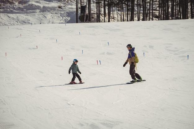 Мать и дочь катаются на лыжах на снежных альпах