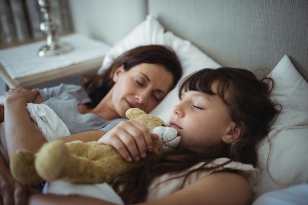 Мать и дочь спят в постели