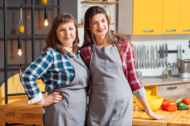 母と娘の笑顔とキッチンでポーズ