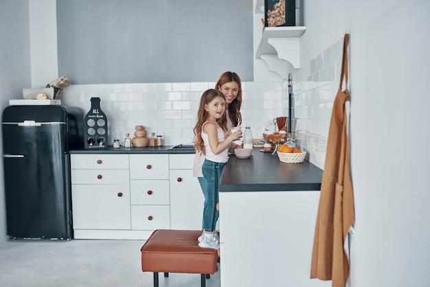 Мать и дочь улыбаются, готовя что-то на кухне