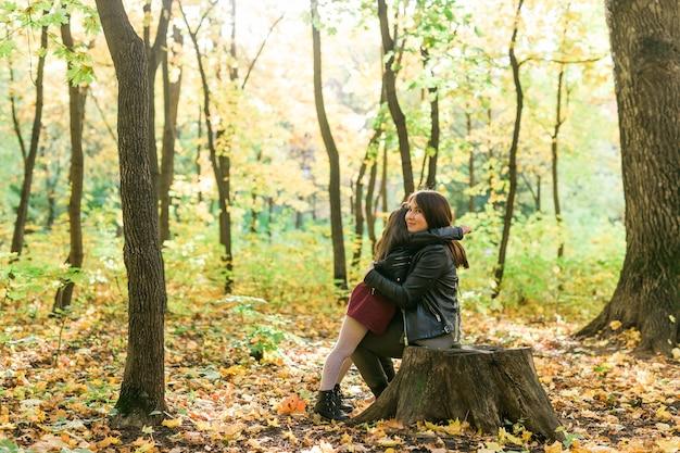 母と娘は秋の黄色い公園の季節とひとり親の概念で一緒に時間を過ごします