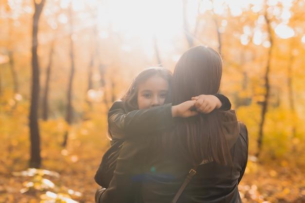 엄마와 딸은 가을 노란 공원에서 함께 시간을 보낸다. 시즌 및 단일 부모 개념입니다.