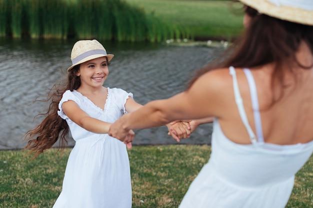 Мать и дочь кружатся у озера