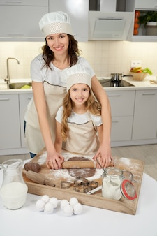 母と娘が麺棒で生地を絞る。