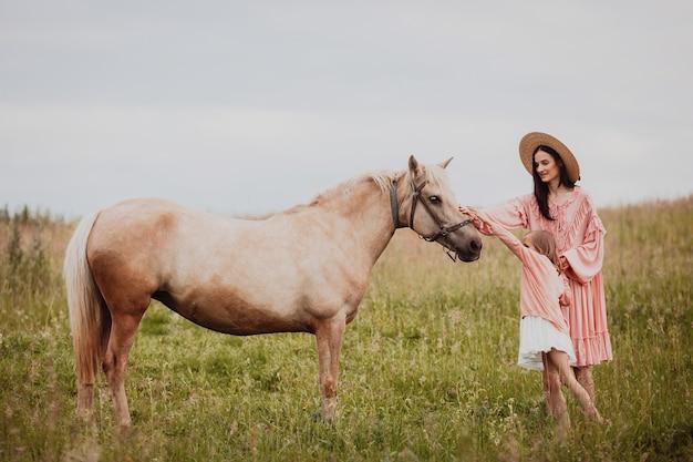 母と娘が馬の前に野原に立つ