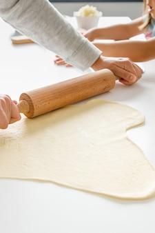 母と娘がピザの生地を伸ばして材料を入れる