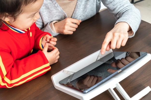 母と娘はタブレットコンピューターでオンラインクラスを勉強します