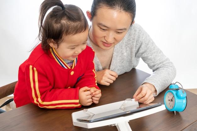Мать и дочь изучают онлайн-класс с планшетным компьютером
