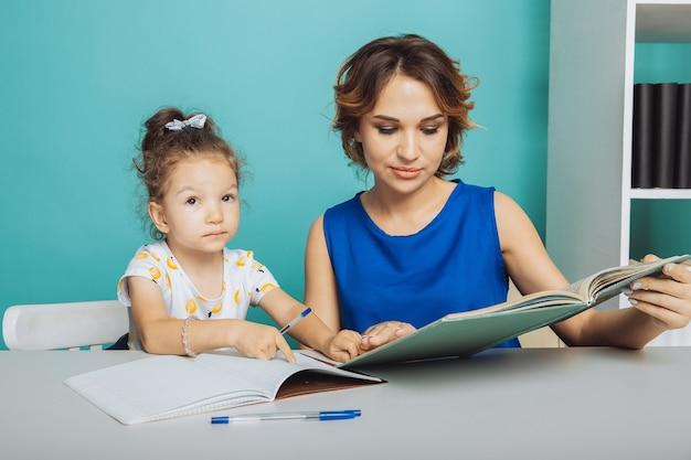 家でテーブルに座って勉強している母と娘。