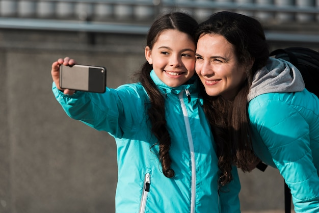 Мать и дочь, принимая селфи на открытом воздухе