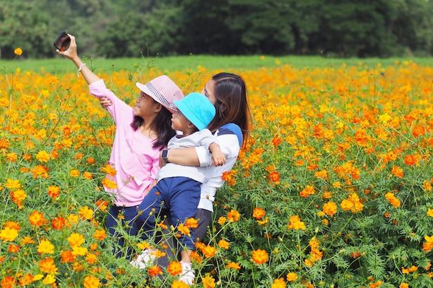 어머니와 딸이 꽃밭에서 전화 selfie와 함께 사진을 복용