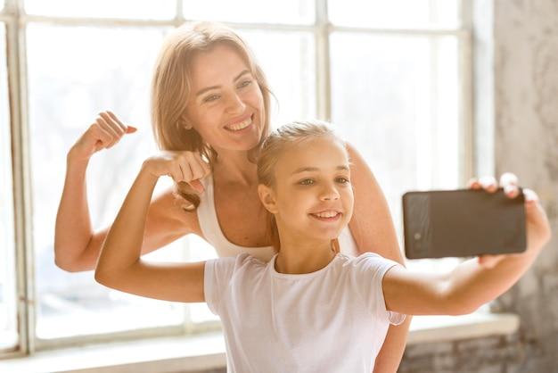 Мать и дочь, принимая селфи, разминая мышцы рук