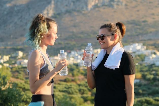 Мать и дочь разговаривают и пьют воду после тренировки