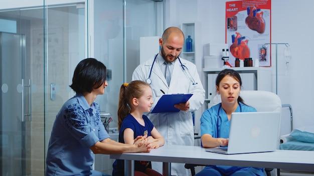 子供の治療について医療従事者と話している母と娘。病院のキャビネットで医療サービス相談診断検査を提供する医学の医師の専門家