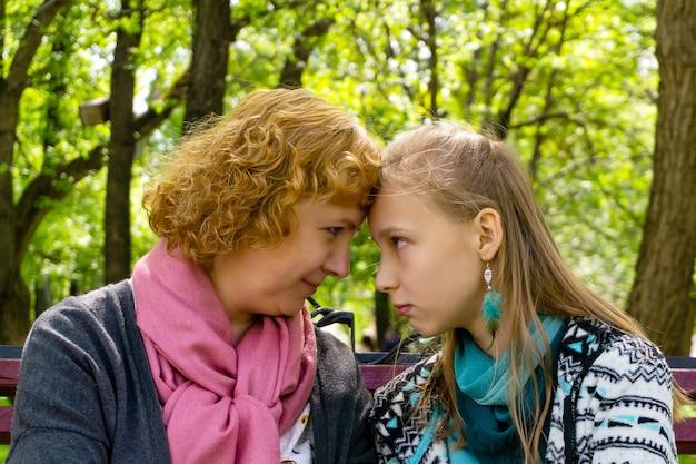 母と娘のティーンエイジャーは、公園のベンチで何かについて内密に通信します