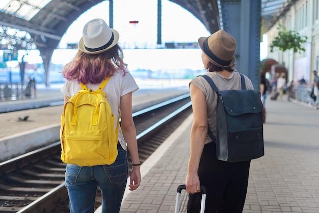 Мать и дочь-подросток с чемоданом рюкзака гуляют на вокзале