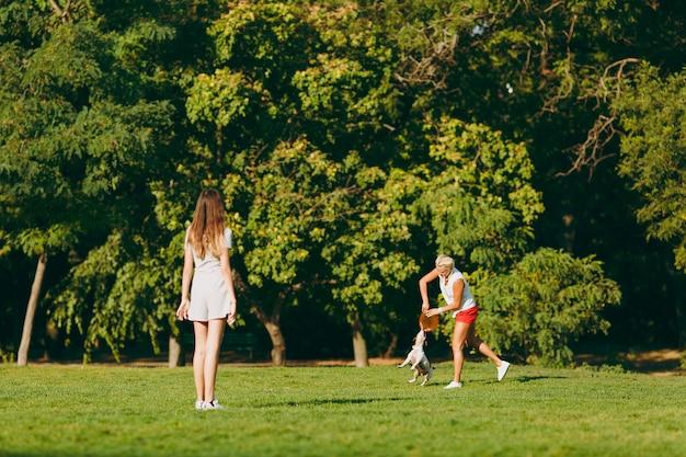 母と娘はオレンジ色のフライングディスクを小さな面白い犬に投げ、緑の草の上でそれを捕まえます。公園で屋外で遊ぶリトルジャックラッセルテリアのペット。犬と女性。野外で休んでいる家族