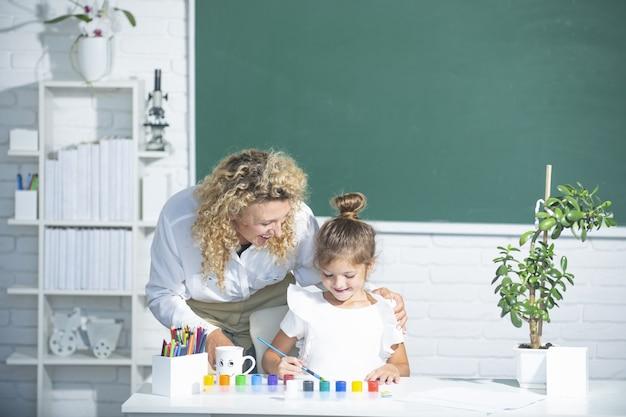엄마와 딸이 함께 페인트. 교사는 학생 아이 소녀를 돕습니다.