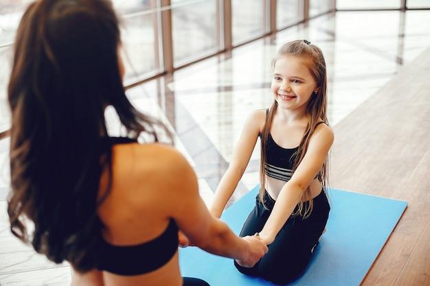 Мать и дочь тренируются в тренажерном зале