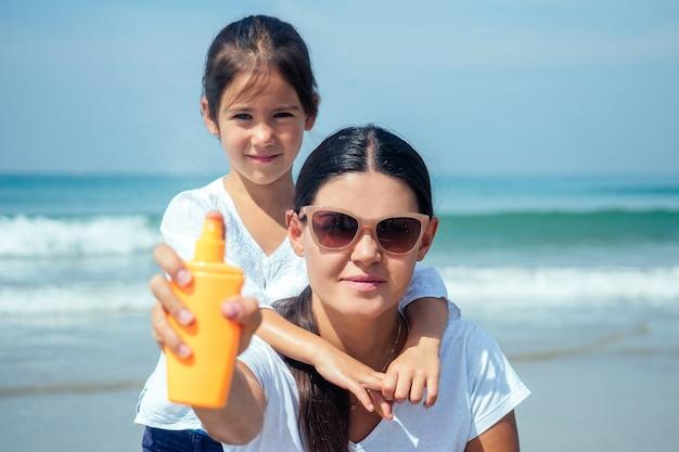 Мать и дочь, используя солнцезащитный крем на пляже