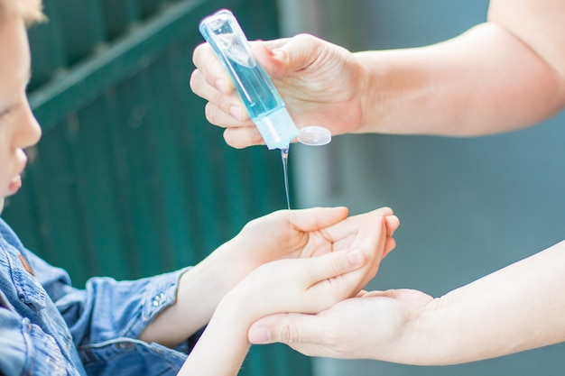 手を洗う消毒剤ジェルを使用して母と娘