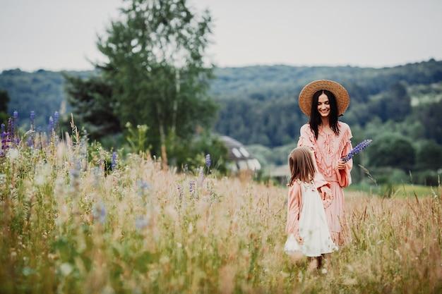 母と娘が緑の畑を歩く