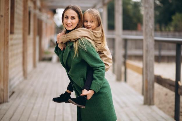 Мать и дочь гуляют по конюшне