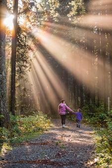 엄마와 딸 태양 광선으로 숲에서 산책