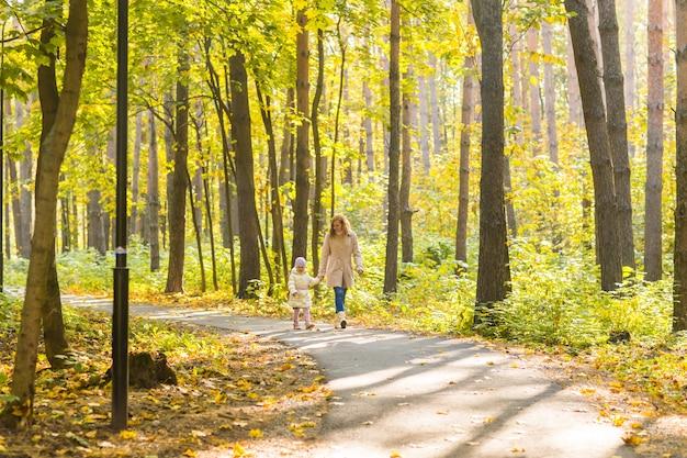 Мать и дочь гуляют в осеннем парке