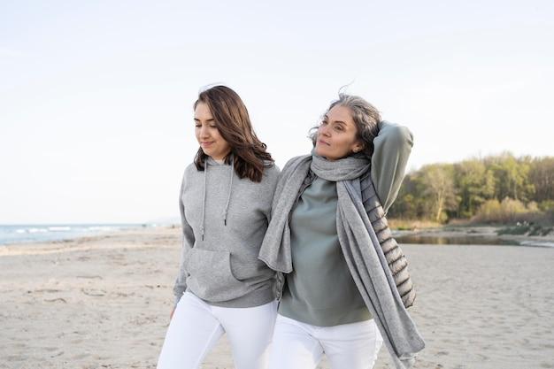 一緒にビーチを歩く母と娘