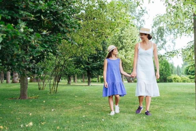 母と娘が一緒に野外を歩いています。