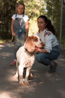 都市公園で犬と一緒に歩く母と娘