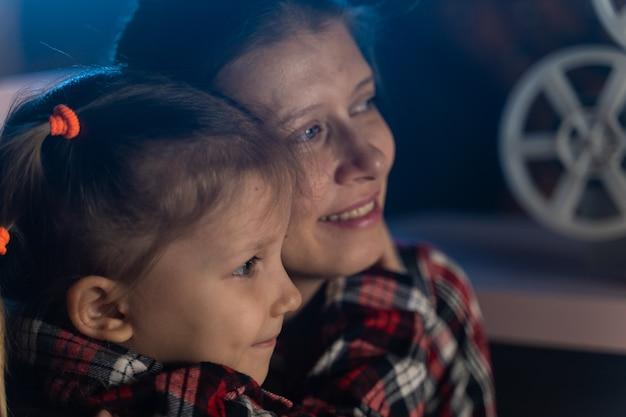 Мать и дочь смотрят старый фильм на ретро-винтажном кинопроекторе дома