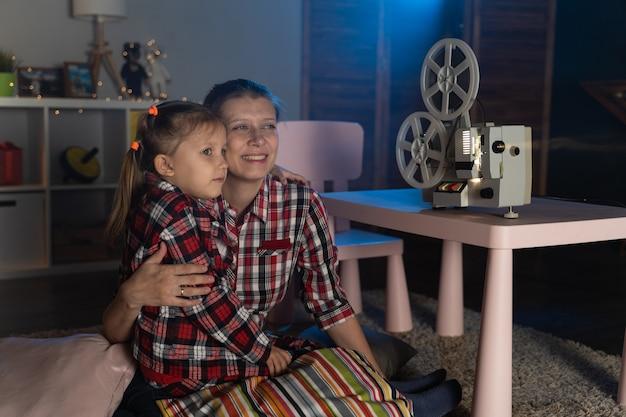 엄마와 딸 집에서 레트로 빈티지 필름 영사기에 오래된 영화를보고
