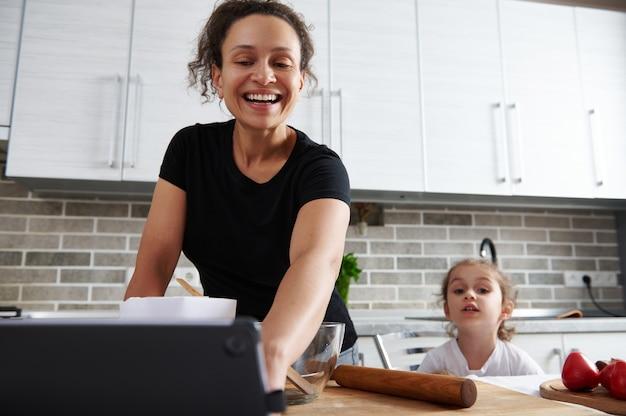 台所に立って、食事のレシピを見ている母と娘。母と娘が一緒に生地を準備します。愛、愛情、優しさ、女性の関係。