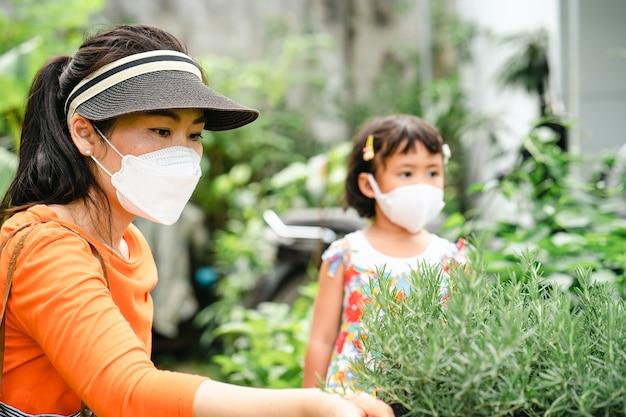木の店でローズマリー植物を選ぶ保護フェイスマスクを身に着けている母と娘