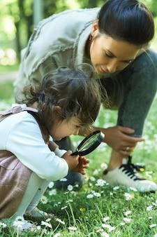 Мать и дочь с лупой изучают ромашковое поле в городском парке