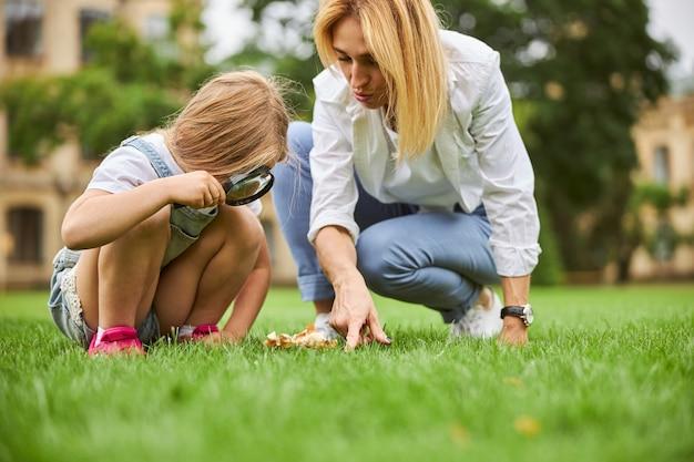 돋보기를 가진 엄마와 딸은 도시 공원에서 푸른 잔디를 탐험하고 있습니다